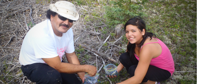 Wayne and Chelsea Powder of Uranuim City picking blueberries<br>Photo courtesy of CanNorth