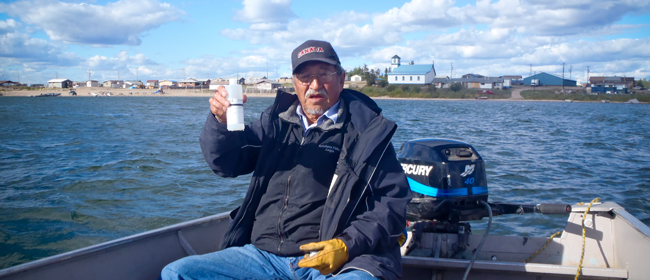Elder Joe Marten from Fond du Lac collecting a water sample<br>Photo courtesy of CanNorth