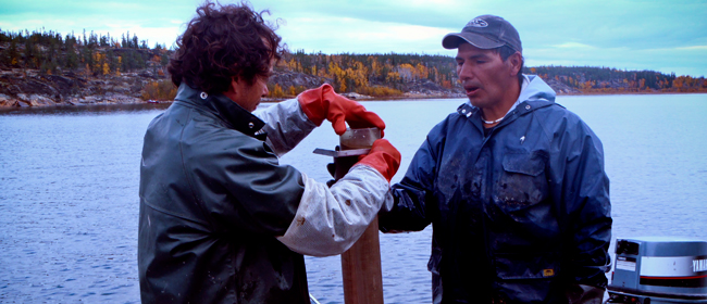 Sandy Powder of Uranium City and Patrick Carrier of CanNorth slicing <br>a sediment core in Crackingstone Inlet - CanNorth Photo